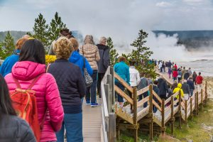 Visitors crowd the boardwalk in the Lower Geyser Basin at Yellowstone. (NPS, Neal Herbert)