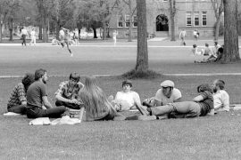 University of Montana students gather in the Oval with Main Hall in the background in the 1970s. (Mansfield Library, University of Montana)