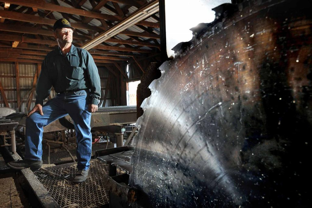 Kelly Gephardt, owner of Gephardt Post Plant & Sawmill, stands in the sawmill of his Roundup, Montana plant. (AP photo/James Woodcock, Billings Gazette.)