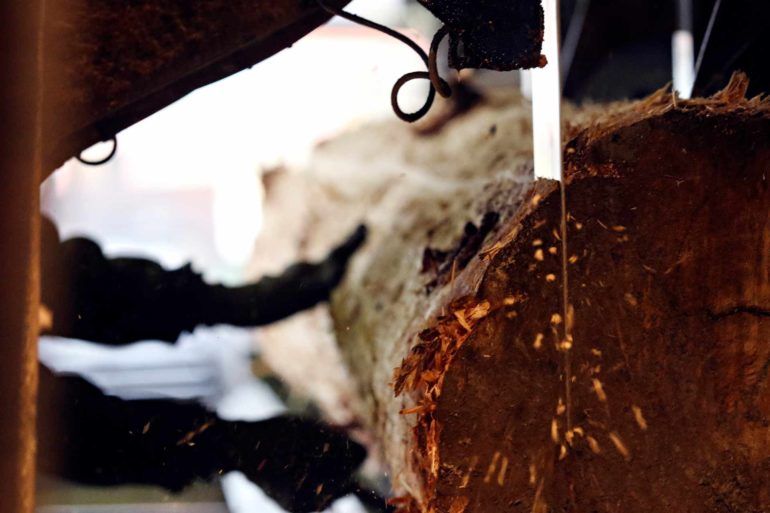 A log goes through a vertical saw at RBM Lumber in Columbia Falls, Montana. (AP Photo/Flathead Beacon, Greg Lindstrom)