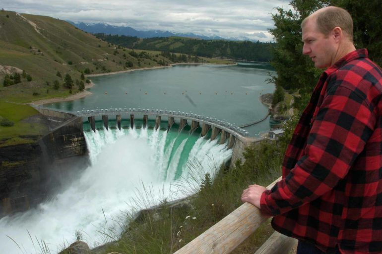 Terry McAllister looks over the Seli'š Ksanka Qlispe' Dam on the Flathead River near Polson, Montana. (AP Photo/Daily Inter Lake, Chris Jordan)