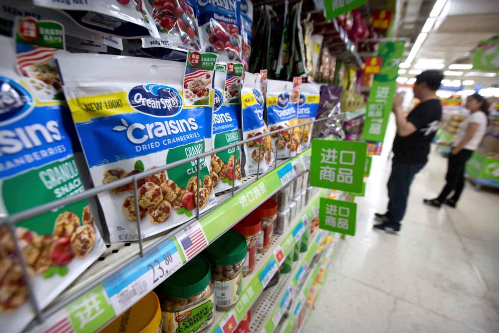 Customers shop near dried cranberry products from the United States at a supermarket in Beijing. China announced higher tariffs on $60 billion worth of American goods in retaliation for American tariffs. (AP Photo, Mark Schiefelbein)