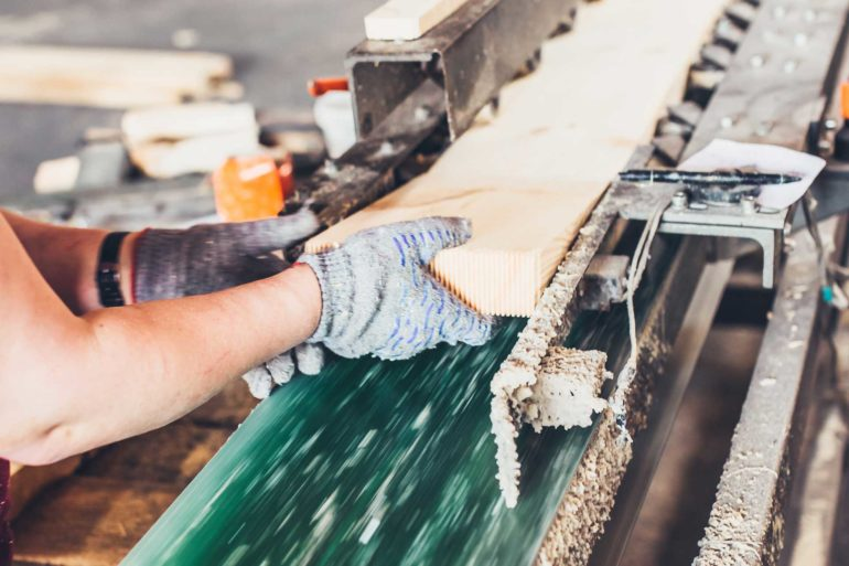 A worker processes wood at a sawmill. (Shutterstock, Vano Vasaio)