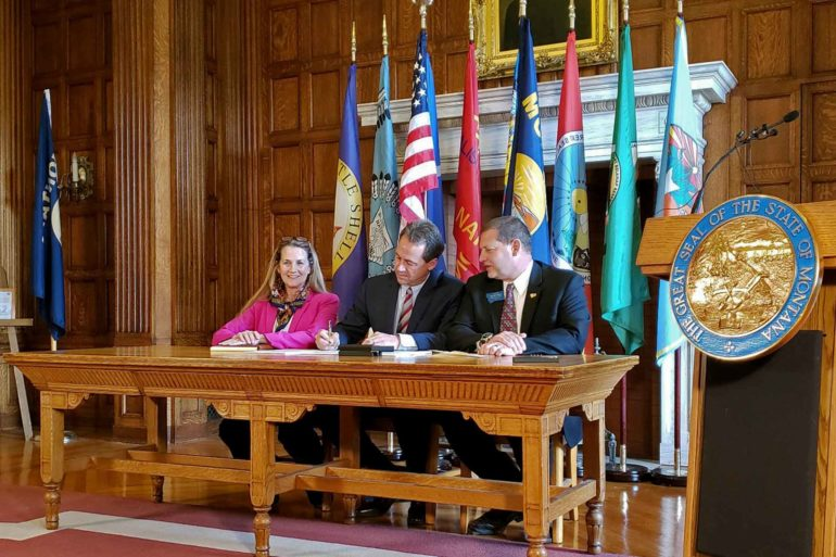Democratic Rep. Mary Caferro, left, and Republican Rep. Ed Buttrey, right, look on as Gov. Steve Bullock signs House Bill 658, reauthorizing Montana's Medicaid expansion program. (AP Photo, Amy Beth Hanson)