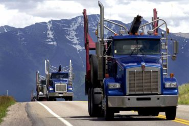 A convoy of log trucks head south on U.S. Highway 93. (AP Photo, Kurt Wilson)