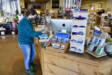 Bella Summers disinfects the cashier stand at The Base Camp in Helena, Montana, on the business's first day open since the lifting of some coronavirus-related closures. (AP Photo, Thom Bridge)