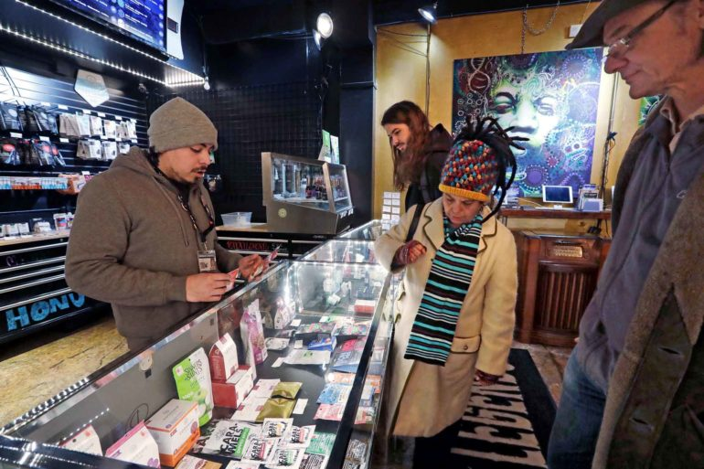 Cannabis consultant Juan Aguilar assists customers shopping for cannabis products in the Herban Legends store in Seattle. (AP Photo, Elaine Thompson)