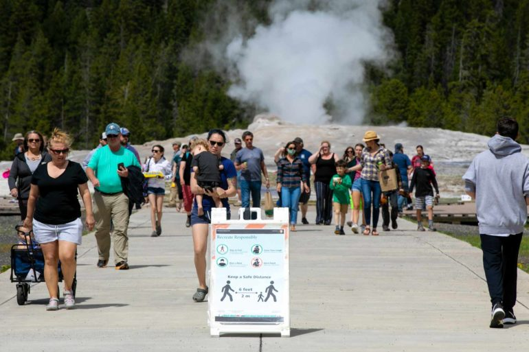 Visitors walk away from Old Faithful as a sign about COVID-19 safety sits in the sidewalk in Yellowstone National Park after reopening in 2020. (AP Photo, Ryan Berry)
