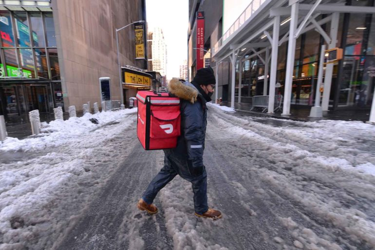 A DoorDash food delivery person makes his way through slushy snow in New York City during a second wave of the COVID-19 pandemic. (AP Photo, Anthony Behar)