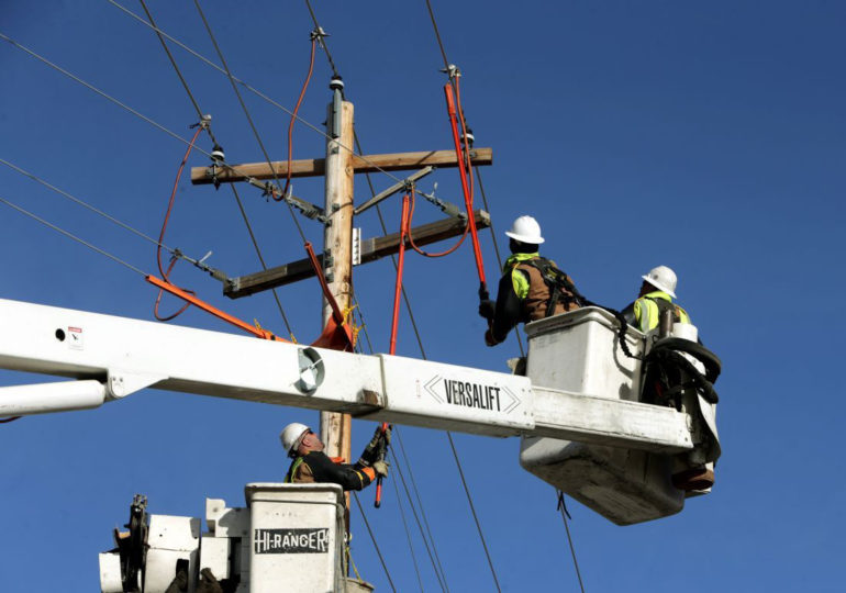 A crew from Yellowstone Valley Electric Cooperative work on a power line on Grand Avenue in Billings. (Casey Page, Billings Gazette)