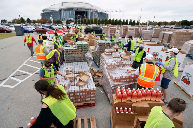 Volunteers build bags of dry goods outside AT&T Stadium during a food distribution event in Arlington, Texas. (AP Photo, Tony Gutierrez)