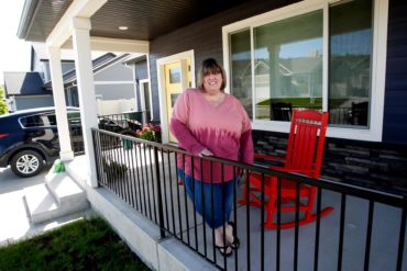 Melisia Muscat stands on the front porch of her new home in Billings that she and her husband bought sight unseen before moving from the Seattle area. (Casey Page, Billings Gazette)