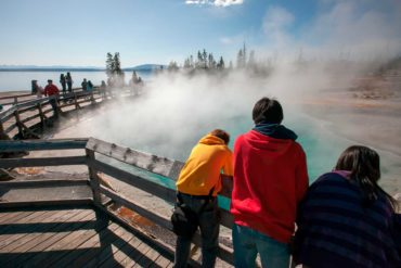 Tourists lean over a railing to observe geothermal features in Yellowstone National Park. (Design Pics, AP Photo)